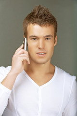 young man in white shirt talking on cell phone