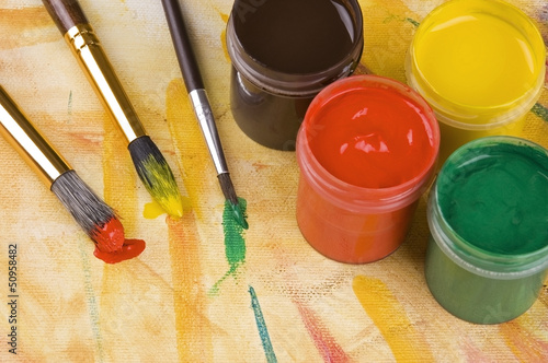 Paints and brushes against painted multicolored background