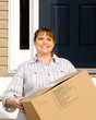 Woman carrying box on moving day in front of home
