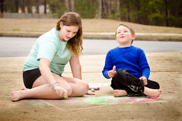 Siblings play with chalk drawing in drive way or sidewalk