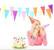 Sad birthday girl with a cake