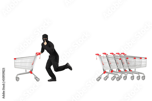 Full length portrait of a robber stealing an empty pushcart