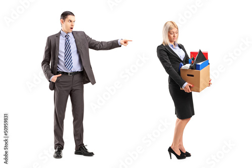 Full length portrait of an angry boss firing a woman with a box