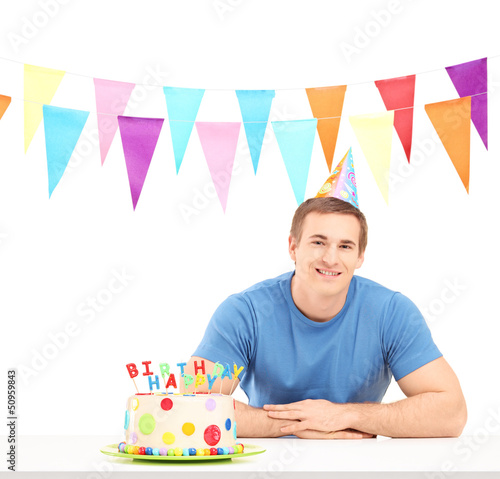 Smiling birthday guy with a party hat and a cake