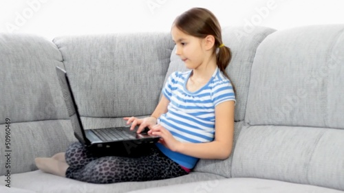 Cute little girl using a laptop in the living room