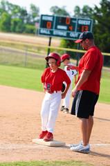 Baseball player and baseball coach at first base.