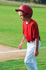 Baseball player walking across field.