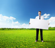 business man whith empty board in hand on field of spring grass