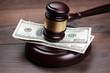 judge gavel and money on brown wooden table