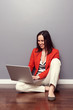 woman sitting on the floor and using laptop