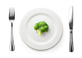 Photo of the fork and knife with white plate and broccoli on whi