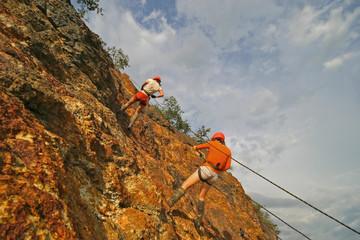 rock climber climbing an overhanging cliff against the blue sky