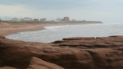 Misty beach on grey day with red rocks in the foreground.  PEI.