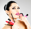 Woman with makeup cosmetic tools near her face.