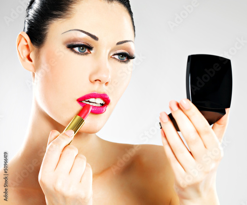 Beautiful woman applying pink lipstick on lips