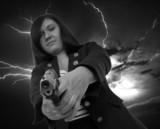woman with handgun and dark sky