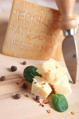Parmesan cheese with knife and fresh basil leaves