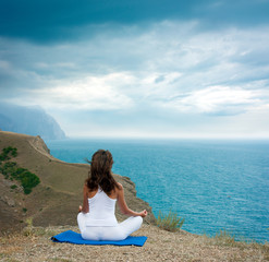 Woman Doing Yoga at the Sea and Mountains