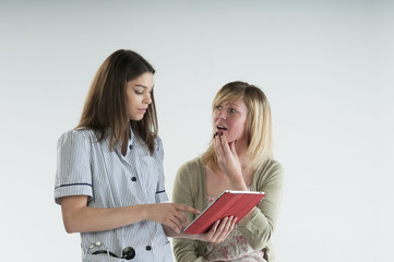 Nurse using an iPad talking to a patient