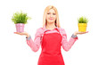 A blond female gardener holding two potted plants