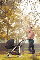A young mother posing with a baby stroller in autumn