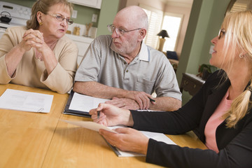 Senior Adult Couple Going Over Papers in Their Home with Agent