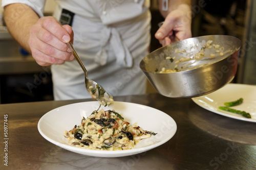 Chef is serving risotto
