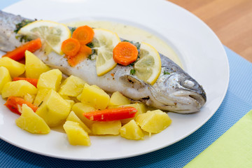 Trout fish with lemon slices and boiled potatoes