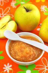 Homemade apple puree in a bowl on colorful tablecloth