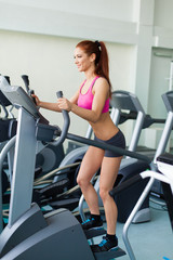 fitness model exercising on a cardio machine in fitness center