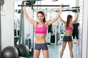 Attractive young fitness model exercising in fitness sport club