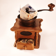 Antique coffe grinder, grinding money, banknotes to coins