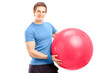 A young male athlete holding a pilates ball