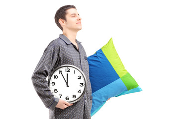 A young man with pillow and clock sleepwalking