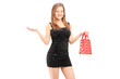 Beautiful young female in black dress holding a bag and gesturin