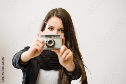 Brunette girl with retro film camera.