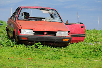 Old abandoned car left in the field.