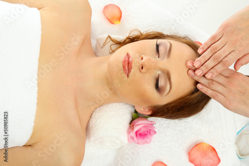 beautiful young woman in spa salon getting massage, isolated