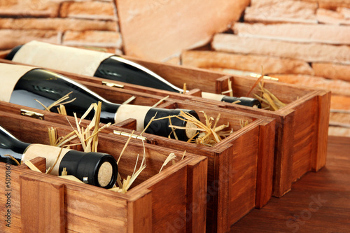 Bottles of old red wine in gift wooden box, on stone background