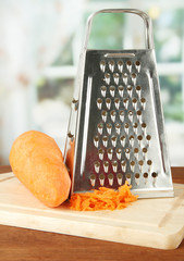 Metal grater and carrot on cutting board, on bright background