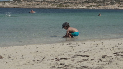 Cute kid playing on the beach, super slow motion