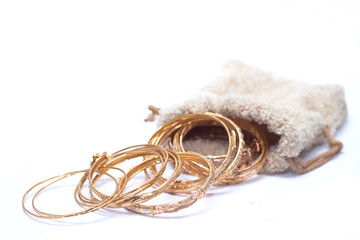 isolated of so many luxury gold jewellery bracelet on pouch