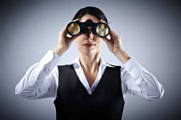 Business woman with binoculars.