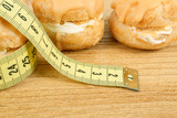 concept of slimming, caramel cakes with measuring tape