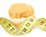 concept of slimming, caramel cake with measuring tape