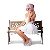 Elegant pinup lady sitting alone on park bench