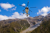 Rescue helicopter fly over mountainous wilderness