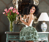 Glamorous Woman in Retro Interior. Vase of Flowers. Reflection