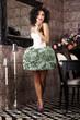 Stylish Brunette standing in Trendy Dress. Modern Interior