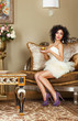 Lady sitting on Retro Couch with Cap of Coffee. Classic Interior